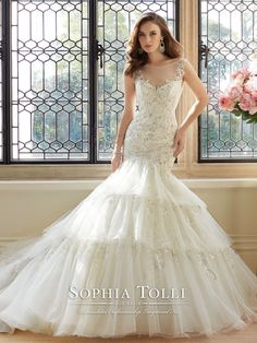 Sophia Tolli - Y11648 – Majestas - Sleeveless misty tulle trumpet wedding dress with tulle bateau neckline, sweetheart bodice features hand-beaded lace appliqués and dropped waist, sheer tulle back bodice edged with appliqués and back zipper both trimmed with diamante buttons, tiered skirt with matching appliqués, chapel length train.  Sizes: 0 – 28  Colors: Ivory/Pewter, White