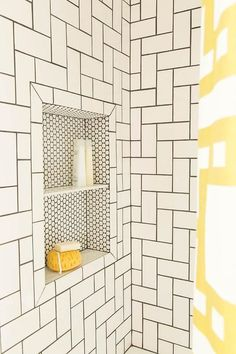 Simple white subway tiles take on a whole new look when laid out in a geometric pattern with dark grout. A penny-tiled shower niche with shelf adds the finishing touch.: