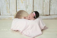 Sweet newborn baby girl in a Moses basket