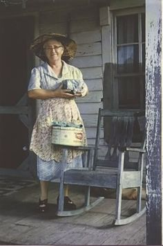 Woman in apron, on porch ~ this looks like my Aunt Christine's house in Texas. If the lady was heavier, it could be Aunt Christine standing there, minus the hat but definitely with the apron. Always an apron.