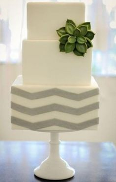 modern, square- tiered, chevron printed, silver and white wedding cake, with a green sugar flower accent