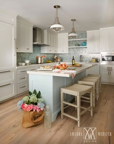 Beautiful white and blue cottage kitchen is equipped with a stunning pale blue kitchen island topped with a white marble countertop seating three tan backless counter stools illuminated by two industrial pendant lights. Tan Kitchen, Blue Kitchen Island, Kitchen Dinning, Kitchen Design, Kitchen Decor, Kitchen Ideas, Beach House Kitchens, Home Kitchens, Coastal Kitchens