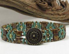 Un très élégant bracelet de perles à l'aide de la populaire deux trou de perles Super Duos et Czechmate tuiles. Ce sont les deux perles de verre pressé faits en République tchèque.  La conception a un peu dune sensation de sud-ouest à lui, mais encore pouvait entrer dans la catégorie contemporaine, aussi bien. Un motif en forme de losange diris bleu métallisé brillant Super Duos alterne avec des rangées de perles dargent tuile. Toho permanent finish galvanisé argent perles ont été utilisés…