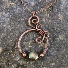 "wire wrapped using various gauges of copper wire. Accenting it is a beautiful peacock green coin pearl and two small copper beads. Pendant measures 1 1/2"" inches in length width: 1"" inch"