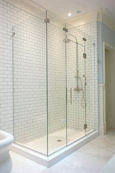 "90 degree corner frameless enclosure with glass bridge, using nickel hardware, ½"" thick starphire glass and 8"" ladder style pull. Glass is coated with Shower Guard protective coating to minimize staining."