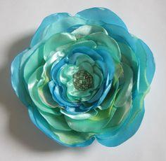 Flor de cetim azul e acqua, com camadas de chiffon.