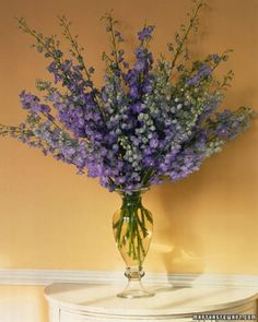 Spiky Delphinium Arrangement: The stems of these cool-blue delphiniums were cut at various lengths to complement the container's curvy shape; the shortest stalks, inserted last, extend only a few inches into the water.