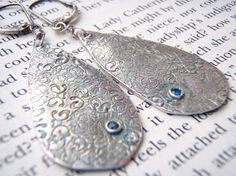 They're made of Precious Metal Clay!!!  I just bought a book on how to do this - now I just need the clay!!