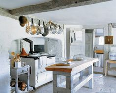 A rough-sawn oak-top island and an Aga stove are some of the sturdy elements in this restored 16th-century farmhouse in West Sussex, England