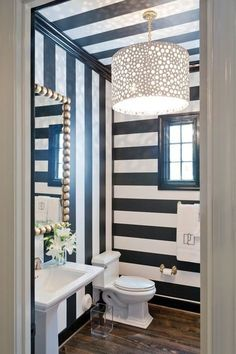 Black and white powder room features a black and white striped ceiling accented with an Oly Studio Meri Drum Chandelier illuminating alternating horizontal and vertical black and white striped walls finished with black crown molding and baseboards. Powder Room Decor, Powder Room Design, Powder Rooms, Striped Room, Striped Walls, Striped Ceiling, Striped Hallway, White Walls, Art Deco Bathroom