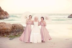 We  Jasmine's beach wedding complete with pretty parasols too. Her bridesmaids are wearing Goddess By Nature Signature Ballgowns in Dust Me Pink colour.