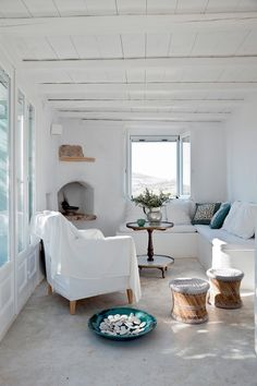 White interior with neutral and pastel accents - adds a hint of colour. Relatively narrow living room which looks bigger thanks to a light colour palette!