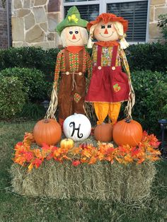 """My 2016 Fall yard decorations. I used a different boy and girl scarecrow this year, a square bale of hay, several plastic pumpkins from the craft store, and 2 fall leaf strands. I spray painted one antique white and stenciled an """"H"""" on it. I used glow in the dark spray paint on the med orange pumpkin. I love how it turned out!"""