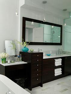 Dark furniture in a white marble bathroom