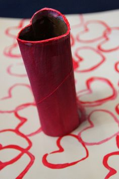Heart stamping using paint and a toilet paper roll.