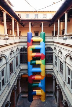 paola pivi inflates oversized, technicolor ladder within palazzo strozzi in florence