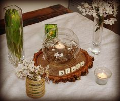 eclectic mix of vases, flowers, tealights, scrabble table numbers and rustic wood base