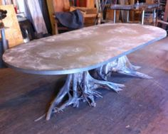 One of a Kind Large Double Tree Root Dining Table with Zinc Oval Top Naturally Weathered Zinc Top with Exceptional Patina Circular Nailhead Riveting on Zinc Top White Cedar Roots, Suitable for Covered Outdoor Use Please Call For Quote Custom Sizing [. Beach Dining Room, Dining Room Table, Dining Rooms, Tree Stump Furniture, Wood Furniture, Furniture Ideas, Zinc Table, Table Bases, Round Outdoor Dining Table