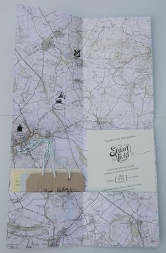 A travel themed wedding invitation wrapped in a map perfect for any destination wedding.