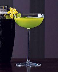 Cholo Fresco       10 mint leaves, plus 1 mint sprig for garnish     2 teaspoons sugar     1/2 ounce fresh lime juice     Ice     2 ounces pisco     1/2 ounce melon liqueur     1 ounce Fresh Cucumber Juice     1 cucumber blossom, for garnish (optional)
