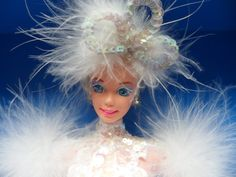 """1994 Snow Princess Barbie® Enchanted Seasons Collection. Barbie doll welcomes you to her winter wonderland!. Fitted in an elegant white sequined gown with marabou feathers, she exudes the true beauty of a snow-filled day. She's sure to melt your heart!. Approximately 12"""" Tall."""