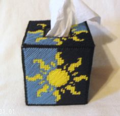 Up for sale is a plastic canvas tissue box cover/Kleenex cozy featuring a classic celestial sun design.  The bright yellow sun is highlighted by two shades of blue, which alternate sides. The same pattern is repeated on all 4 sides of the tissue cozy.  This Kleenex cozy fits a standard, bouti...