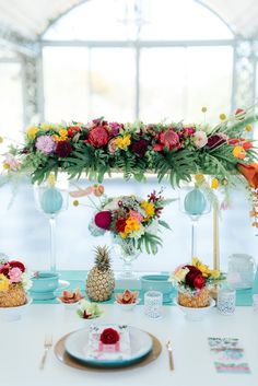 Bright and beautiful tropical tablescape filled with flowers, ferns, pineapples and hand painted details.
