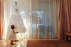 A young flower girl admires a beautiful wedding dress.