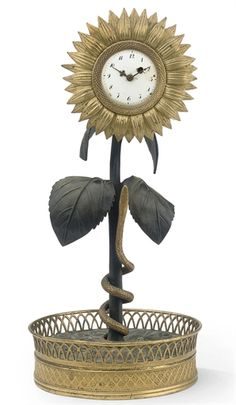 A RESTAURATION ORMOLU AND PATINATED BRONZE SUNFLOWER TIMEPIECE  FIRST QUARTER 19TH CENTURY  The naturalistically cast sunflower with a detachable bezel inset with a watch movement (unsigned) with white enamel dial and ormolu hands above a stem with a coiled serpent, the cast base surrounded by a pierced rim, possibly originally with an ormolu encrier base, now lacking.
