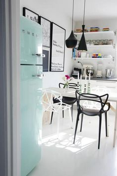 What a great kitchen/informal dining room. The black & white colour theme, with the pops of colour, including the mint Smeg fridge. The Tom Dixon pendant lights are amazing, and so are the Kartell Masters chairs.