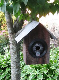 Size: 14.25 (w) x 14.25 (h) x 9.5 (d) - dimensions include corregated tin roofing measurements    Bring a little music nostalgia to you garden with this decorative bird house. Made from reclaimed barn wood from Phlox, Wisconsin from the now retired farm that has been in my family for 4 generations. Remnants of the original red barn paint is still visable on this 100+ year-old barn wood. It features a vintage 45 rpm vinyl record as the entry way facade with an appropriate title for your…