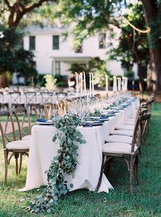 long tables with a eucalyptus garland   Cassidy Carson