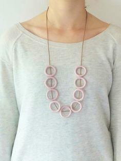 Cercles de lunatique modelées en argile polymère, monté sur un cordon en coton ciré marron clair. Le fond en bois montre la couleur rose plus correcte. Parfait pour ceux qui recherchent quelque chose de sobre, ludique et chic. Aime ces pastels, elles se portent avec toutes les