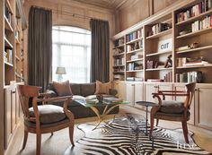 For the library, an existing sofa upholstered in a Dorian Bahr textile and the clients' antique Biedermeier armchairs, featuring a Holly Hunt suede purchased at George Cameron Nash, surround a vintage cocktail table from Jon Vaccari Design in New Orleans. A Mattaliano side table rests on a zebra rug.