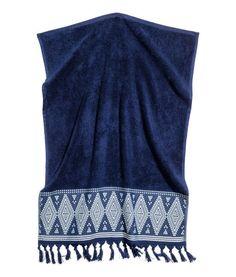 Mørkeblå. Håndklæde i blød bomuldsfrotté med broderet mønster og kvaster forneden. Strop i den ene korte side.