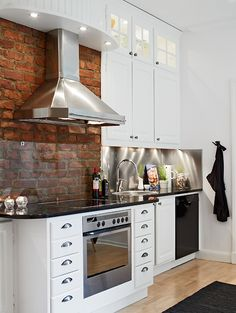 Chic White Kitchen with Brick & Stainless Steel. Note the plexi backsplash over the brick. Board above fan