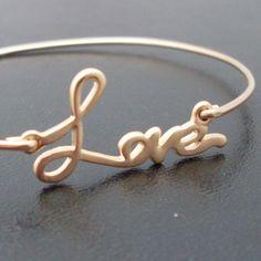 Ein vergoldetes love wurde in einen eleganten Armreif mit vergoldeten Band verwandelt.    Dieses klein handgeschriebene Liebeszeichen Love ist das pef