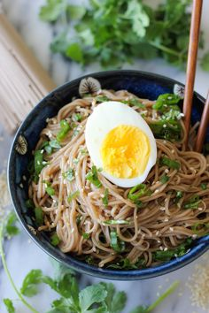 Ingredients: 8 ounces soba 1/4 cup rice wine vinegar 2 tablespoons soy sauce 1 tablespoon sesame oil 1 tablespoon sugar 1 clove garlic, pressed 1 teaspoon grated ginger 2 green onions, thinly sliced 2 tablespoons chopped fresh cilantro leaves 1 teaspoon sesame seeds 2 hard boiled eggs, sliced lengthwise, for serving