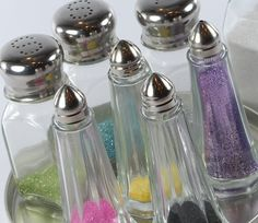 Reuse salt and pepper shakers as containers for glitters. The small holes minimizes the application of glitter and mess!