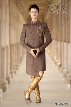 This elegant GTC- Classic Sherwani is a seamless blend of grace and class fabricated on Silky Jacquard fabric. It is finely festooned with intricately and meticulously detailed regal hand-beaded work on the collar and front-panel. It has a charming asymmetrical cut along with an uniquely stylized design. It is paired with a gold churidar. Design-style & Color-scheme customizations available.   Sherwani Groom, Wedding Sherwani, Mehndi Ceremony, Gold Outfit, Jacquard Fabric, Churidar, Fashion Show, Fashion Design, Mandarin Collar