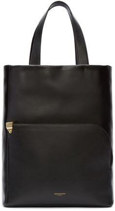 Structured buffed leather tote bag in black. Twin carry handles at top. Patch pocket with wraparound zipper and logo printed at bag face. Raised leather detailing at base. Zippered pouch and patch pocket at suede lined interior. Gold-tone hardware. Tonal stitching. Approx. 15