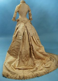 """Silk faille wedding gown, 1870's. Densely embroidered front panel on the skirt, echoed on the bodice: naturalistic flowers and vines inc. lily of the valley.  Trimmed w/ Brussels lace. Seller says it's a one-piece ensemble, which is quite unusual. Very clean construction. Swags and box pleats at the back and train, lined in netting with dust ruffle interior hem. Chest ~32"""", waist 22"""", length in front 51"""", train 80""""."""