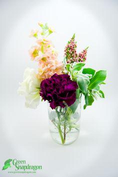Centerpiece arrangement in wine bottle vase with stock, alstroemeria, carnation, snow on the mountain, wax flower.