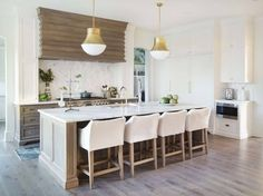 """The true star of this show is the custom hood. """"The oak hood is a one-of-a-kind Castle design with a scalloped cut and wax finish that gives it an aged look."""" See more photos of this beautiful space at styleblueprint.com! Interior Designer: Castle Homes Image: Reed Brown Photography"""
