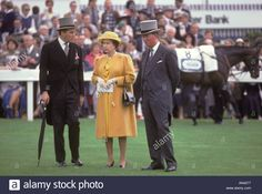 Lord Porchester the Earl Carnarvon (left) Queen Elizabeth in yellow dress with courtier at Derby Day horse race Epsom Downs Surrey 1985. 1980s UK Stock Photo Yellow Coat, Yellow Dress, Courtier, Uk Images, Derby Day, Horse Racing, Surrey, Revolutionaries, Queen Elizabeth