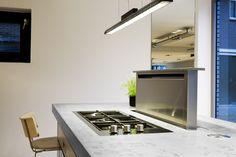 Arclinea keuken met afzuigkap in het werkblad. Door in de keuken te kiezen voor een afzuigkap die uit het aanrechtblad omhoog komt, houd je de ruimte open en overzichtelijk. Hier is er gekozen voor een subtiele lamp aan draden die luchtig oogt. Verder is ervoor gekozen om het werkblad aan de zijkant een stukje over te laten steken zodat er een tafelblad ontstaat. Arclinea, foto Abe van Ancum