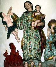 Bronte, chiesa di S. Giovanni, Statua della Madonna del Lume- Un particolare della Statua della Madonna del Lume con Gesù Bambino: la Vergine regge con la mano destra un peccatore nell'atto di precipitare all'inferno. Alla sua sinistra un angelo sorregge un cestino con i cuori dei peccatori convertiti.