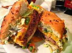 The Gridiron Burger - A delicious cheeseburger and nachos in one! It all starts with a fresh 1/2 lb. Angus patty with melty Pepper Jack cheese, and crisp lettuce, then, thrown on top of that, a pile of nachos built with a crisp heaping helping of Doritos nacho chips, melted cheddar cheese, sour cream, black olives, fresh guacamole and salsa.