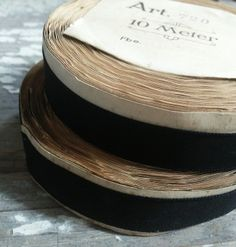 Beautiful black grosgrain ribbon on the original rolls.Creamy paper lining remains to protect the ribbon and a labels are featured on one or both sides.4