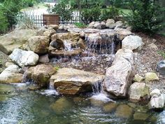 A custom yard pond & waterfall built by Living Waterscapes in Greensboro, NC.
